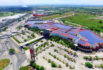 Aerial view shopping center mall red roof top solar panels parking lot